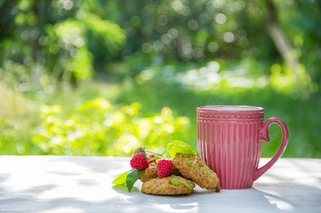 Tazza di tè e biscotti di farina d'avena nel giardino estivo