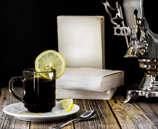 Tazza di tè e una vecchia samovar su fondo di legno