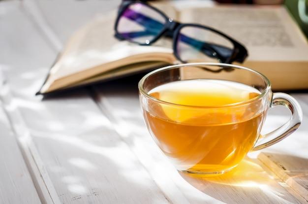 Tazza di tè, libro aperto e occhiali da vista con ombra solare