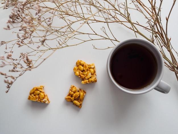 Tazza di tè, kozinak dell'arachide e fiori secchi su un bianco.