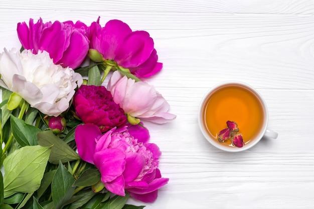 Una tazza di tè e fiori di peonie su un fondo di legno bianco
