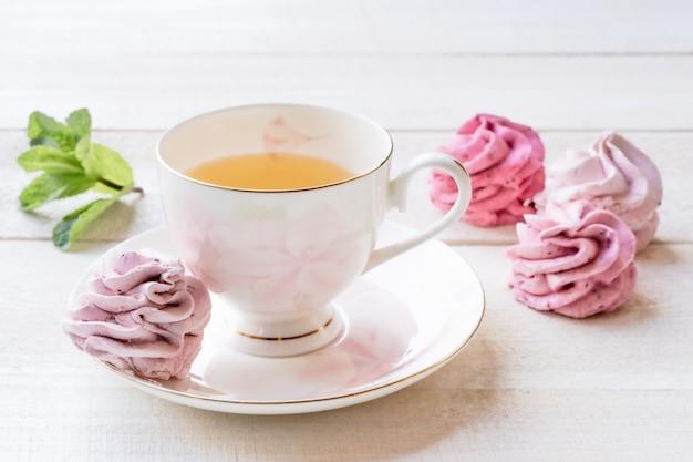 Tazza di tè e caramella gommosa e molle rosa e tè verde su bianco. cibo. confetteria e bevande