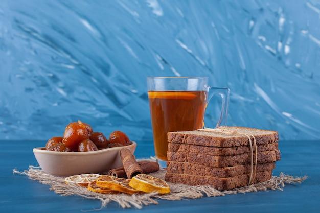 Una tazza di tè, pane a fette e marmellata di fichi su un asciugamano, su sfondo blu.