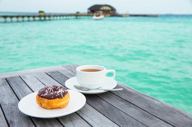 Una tazza di tè sul tavolo con il mare sullo sfondo