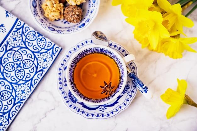 Una tazza di tè con anice stellato e limone, piatti bianchi e blu e narcisi gialli primaverili