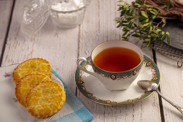 Tazza di tè con biscotti su una tavola di legno bianca