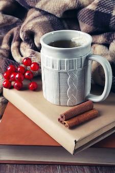 Tazza di tè con il libro sul primo piano del tavolo