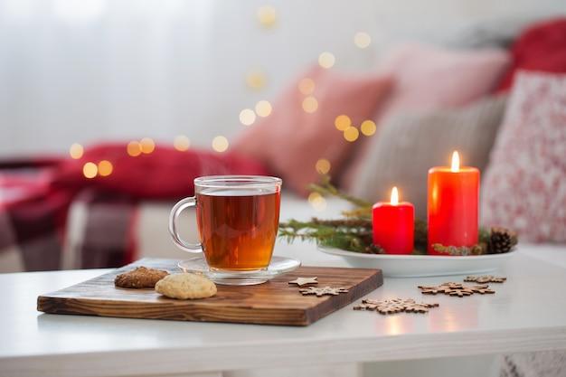 Tazza di tè con candele accese a casa