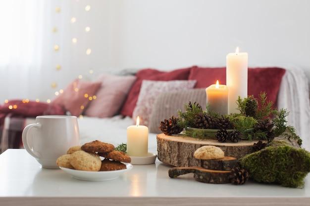 Tazza di tè con candele accese sul tavolo bianco