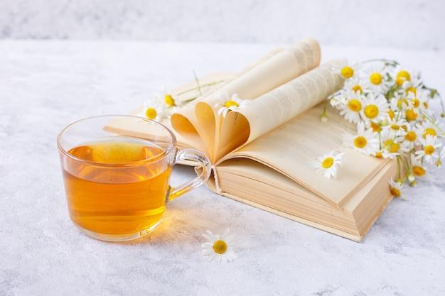 Una tazza di tè alla camomilla e un bouquet di margherite in un vaso