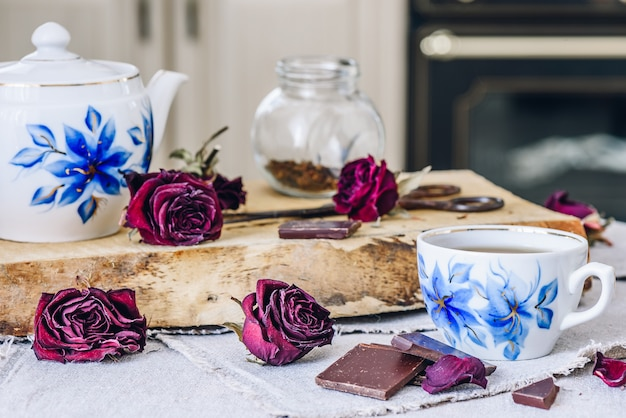 Tazza di tè con barrette di cioccolato, boccioli di rosa secchi e teiera con barattolo e forbici arrugginite a bordo.