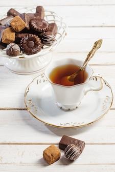 Tazza di tè con la caramella di cioccolato sulla tavola di legno bianca