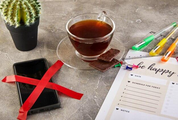 Tazza di tè al cioccolato e un telefono sul tavolo