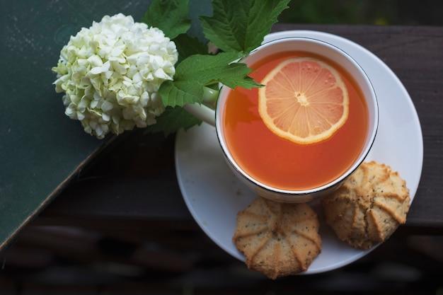 Una tazza di tè con biscotti e un vecchio libro e un fiore di buldanezh su una terrazza aperta in estate, piatta