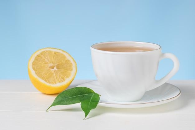 Una tazza di tè con mezzo limone su un tavolo bianco su sfondo blu. una bevanda tonificante utile per la salute.