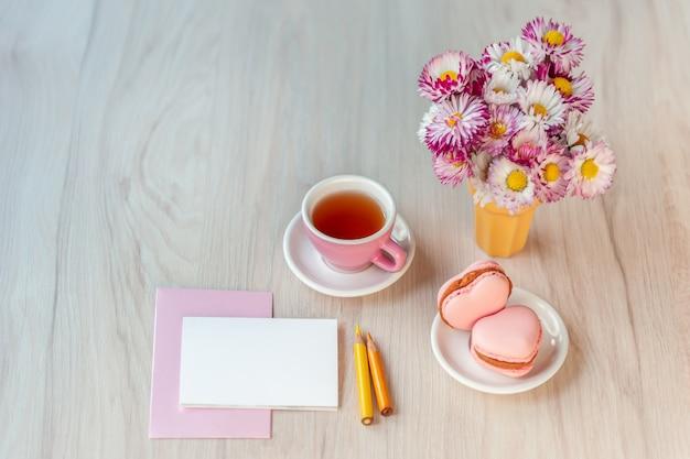 Una tazza di tè con macarons a forma di cuore