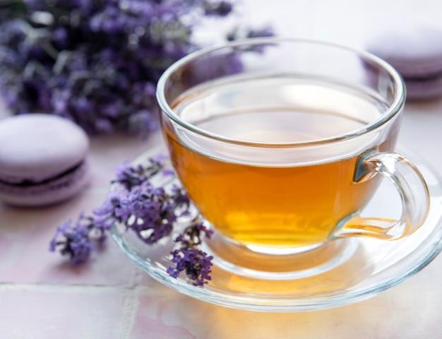 Tazza di tè con dessert amaretto al gusto di lavanda su sfondo di piastrelle rosa