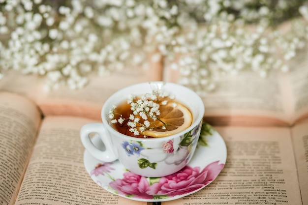 Tazza di tè al limone e libro aperto sul tavolo in camera