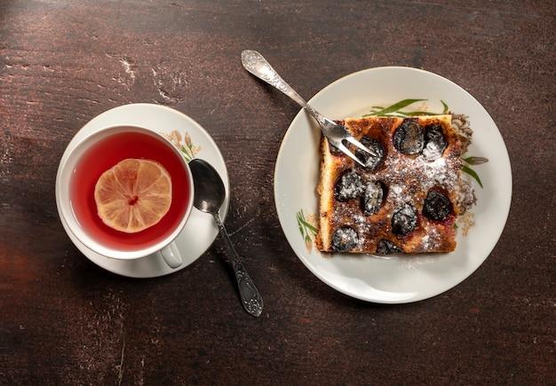 Tazza di tè con torta al limone e prugne su un tavolo di legno
