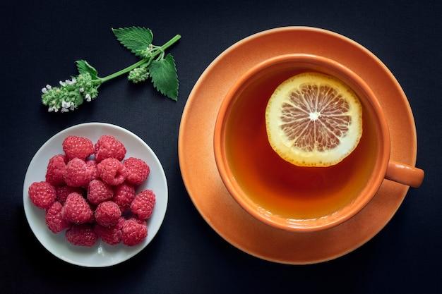 Tazza di tè al limone, un piattino con lamponi freschi e un rametto di melissa su uno spazio buio
