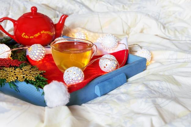 Tazza di tè con limone su un vassoio sul letto a letto comfort inverno mattina