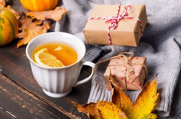 Tazza di tè al limone sul tavolo scuro in legno con foglie d'autunno, zucche. arredamento autunnale, atmosfera autunnale, natura morta autunnale. concetto di stagione autunnale. ringraziamento e festa di halloween. distesi, copia spazio