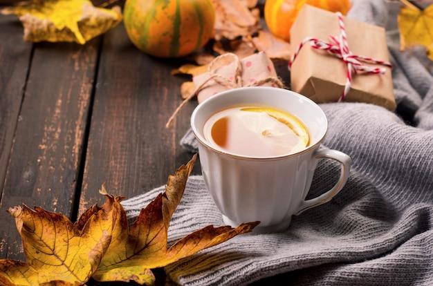 Tazza di tè al limone sulla tavola di legno scuro con foglie di autunno