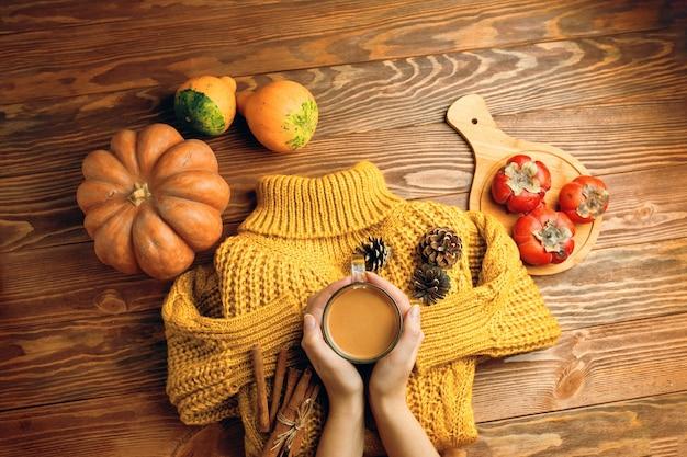 Tazza di tè con pigne al latte e bastoncini di cannella su maglione lavorato a maglia giacca arancione zucche e sw...