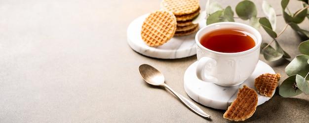 Tazza di tè con mini stroopwafel, biscotti syrupwaffles e rametti di eucalipto su superficie chiara con spazio di copia. banner