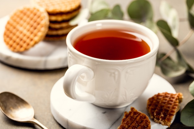 Tazza di tè con mini stroopwafel, biscotti syrupwaffles e rametti di eucalipto su superficie chiara