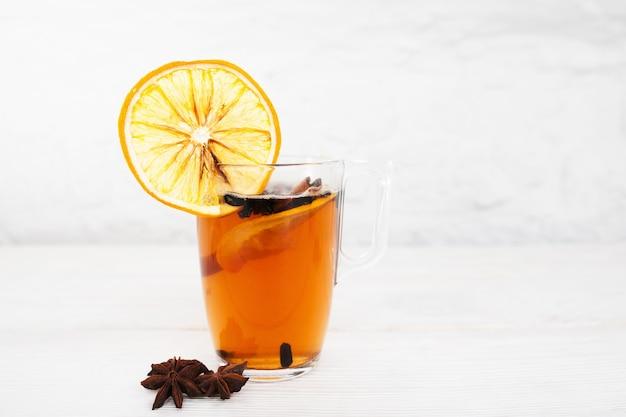 Tazza di tè con arancia e cannella su bianco