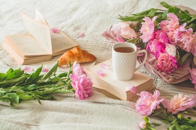 Tazza di tè con fiori di pions e decorazioni primaverili sui libri