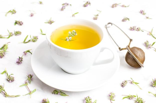 Una tazza di tè con fiori di timo su uno sfondo bianco. la vista dall'alto. concetto di medicina popolare.