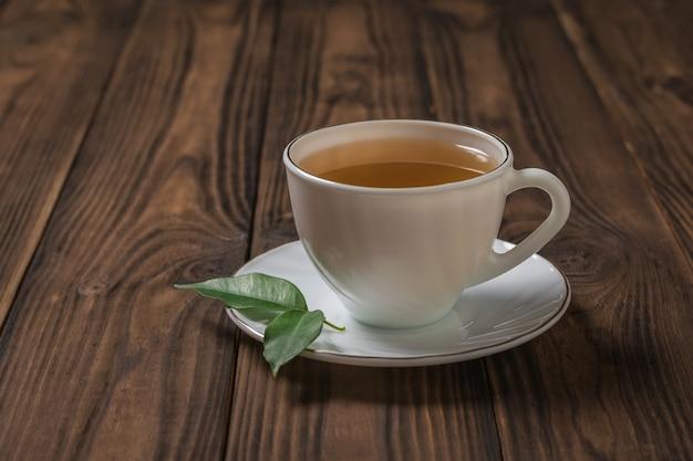 Una tazza di tè con due foglie verdi su un tavolo di legno. una bevanda tonificante utile per la salute.