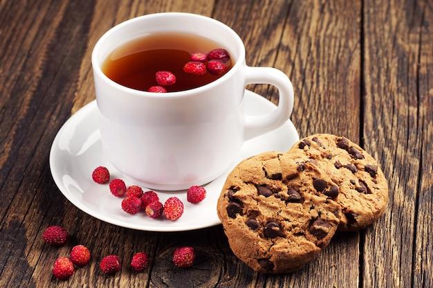 Tazza di tè con fragoline di bosco e biscotti al cioccolato dolce