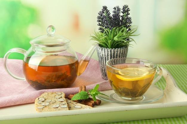 Tazza e teiera di tè verde con biscotti sul tavolo