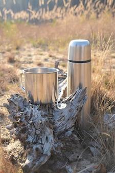 Una tazza e un thermos stanno a terra