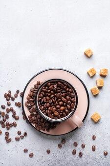 Tazza con chicchi di caffè all'interno su cemento grigio