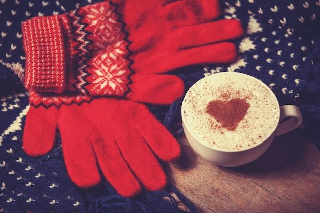 Tazza con caffè e forma di cuore di cacao su di essa e sciarpa
