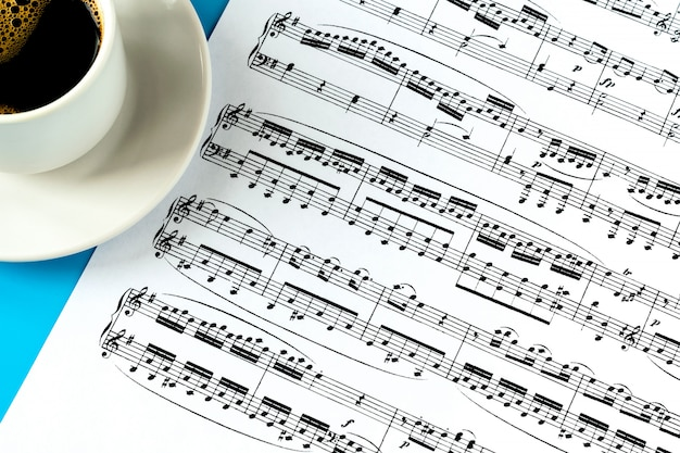 Tazza di caffè su un piattino bianco e un foglio con note musicali su un blu