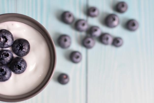 Tazza con delizioso yogurt e mirtilli su sfondo di tavole blu. cibo dietetico sano.