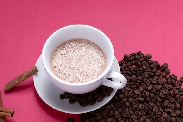 Tazza con latte espresso e isolato su sfondo rosa pink