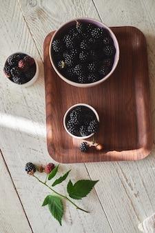 Tazza con more nere e rosse fresche su un vassoio marrone, foglie di mora verde è sul tavolo. sfondo di legno chiaro