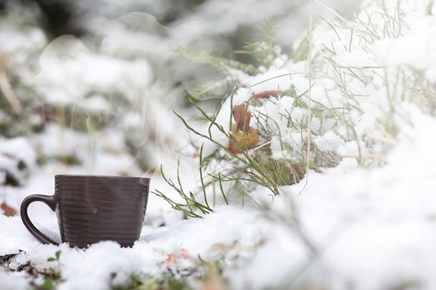 Una tazza con una bevanda calda nella foresta invernale. cioccolata calda con cannella sullo sfondo della foresta invernale. prima neve e cioccolata calda.