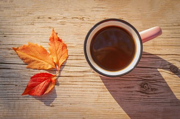 Tazza con bevanda calda su un tavolo di legno vicino alle foglie autunnali in una giornata di sole, vista dall'alto