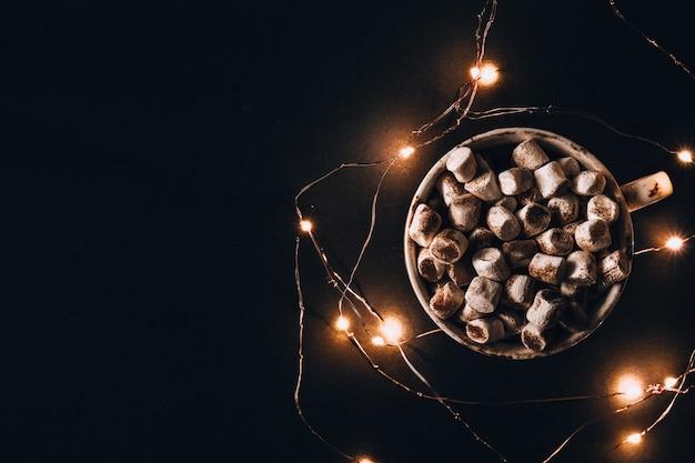 Tazza con cacao caldo invernale e marshmallow durante la notte. luci della ghirlanda di natale. buona notte e sogni d'oro. giornate invernali accoglienti. hygge.