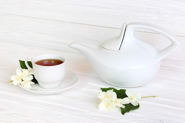 Tazza con tè al gelsomino e fiori di gelsomino su uno sfondo di legno chiaro