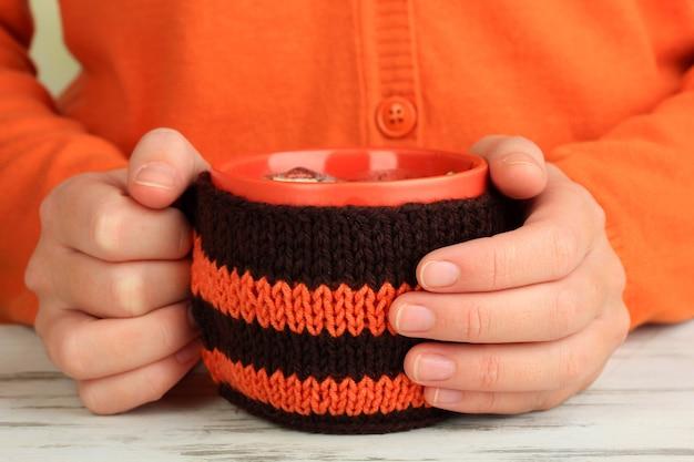 Tazza con cosa lavorata a maglia su di esso nelle mani femminili si chiuda