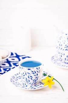 Tazza con motivo a foglie, tè blu e piccolo narciso, copia dello spazio