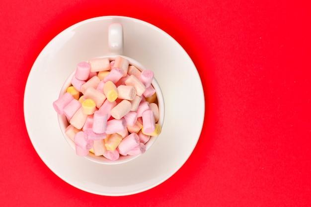 Coppa con marshmallow su uno sfondo rosso. copia spazio.